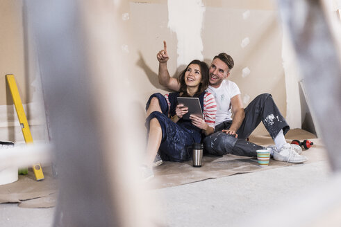 Young couple on construction site of their new home, using digital tablet - UUF10107
