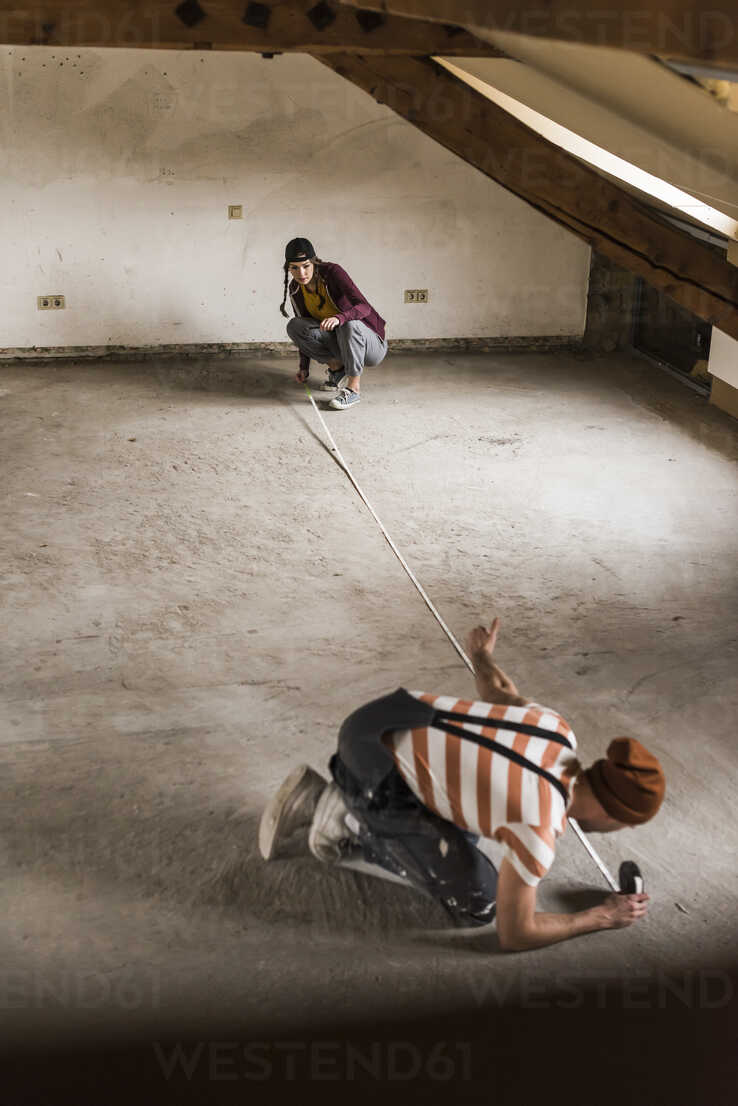 Young man and woman measuring floor on construction site - UUF10125 - Uwe Umstätter/Westend61