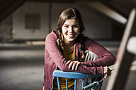 Young woman sitting on construction site of her new home - UUF10140
