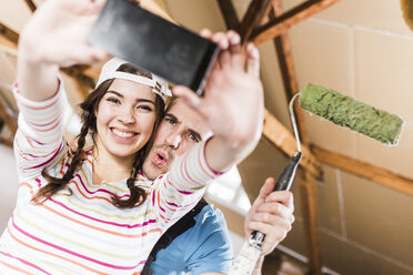 Young couple renovating their new home, taking smart phone selfies - UUF10143