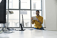 Young businessman in office using digital tablet - SBOF00299
