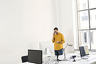 Young businessman in office talking on the phone - SBOF00305