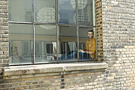 Young professional at the window looking confident, using laptop - SBOF00308