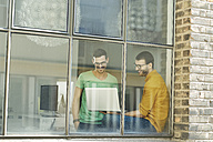 Young professionals at the window using laptop - SBOF00311