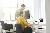 Two businessmen working together in office, using laptop - SBOF00320