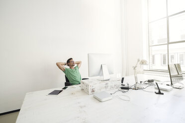 Young businessman in office relaxing at desk - SBOF00323
