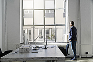Young businessman looking out of office window - SBOF00326