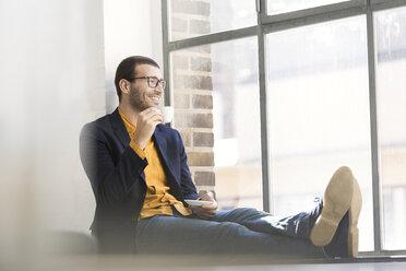 Businessman sitting on window sill, drinking coffee - SBOF00329
