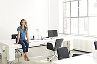 Casual businesswoman in office, sitting on desk, looking confident - SBOF00332