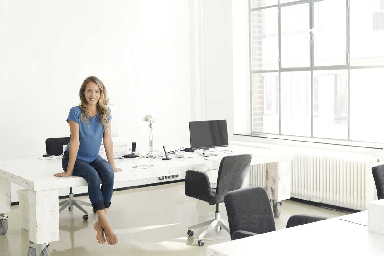 Casual businesswoman in office, sitting on desk, looking confident - SBOF00332 - Steve Brookland/Westend61