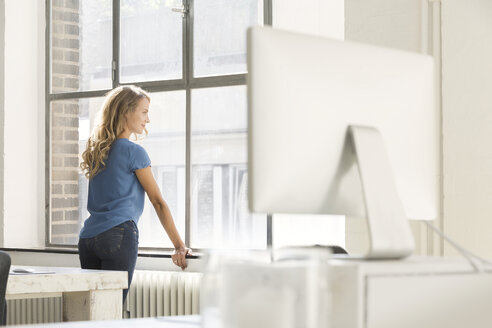 Casual businesswoman in office looking out of window - SBOF00335