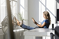 Casual businesswoman in office using digtal tabet with feet on window sill - SBOF00338