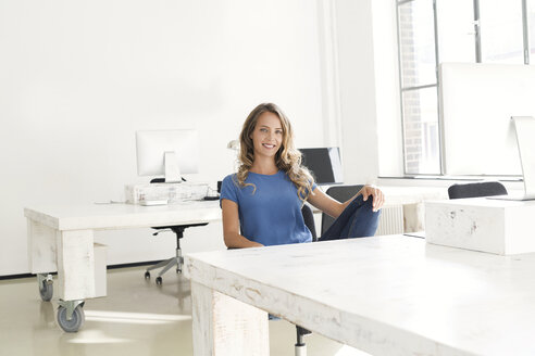 Casual businesswoman sitting in office - SBOF00341