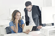 Young man and woman working together in office - SBOF00344