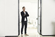 Young businessman standing in his office with arms crossed - SBOF00347