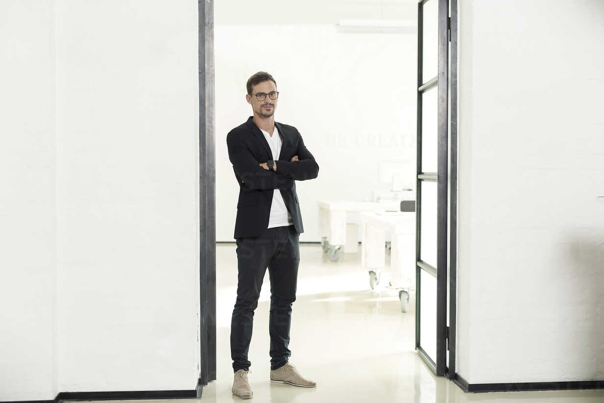 Young businessman standing in his office with arms crossed - SBOF00347 - Steve Brookland/Westend61