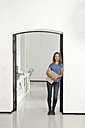 Casual businesswoman in office leaning against door frame, holding folder - SBOF00350