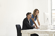 Young man and woman working together in office - SBOF00356