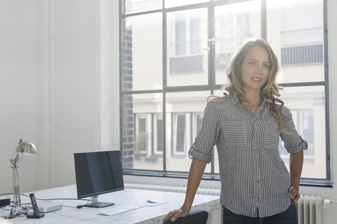 Businesswoman standing in her office, looking at camera - SBOF00365