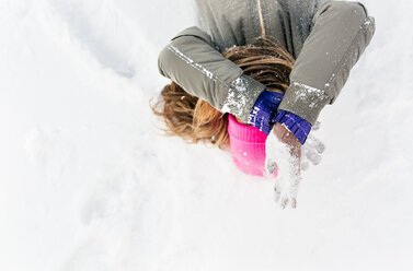 Young woman lying in the snow, covering her face - MGOF03028
