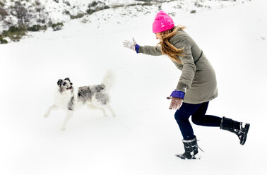 Young woman playing with her dog in the snow - MGOF03031