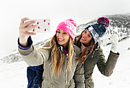 Two friends taking smart phone selfies in the snow - MGOF03055