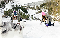 Two friends playing with their dog in the snow - MGOF03061