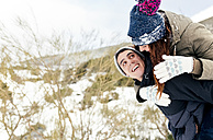 Young man carrying his girl fried piggyback in winter - MGOF03070