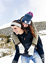 Young man carrying his girl fried piggyback in winter - MGOF03073