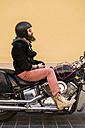 Bearded biker wearing helmet and sunglasses sitting on his motorcycle - KKAF00492