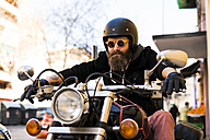 Portrait of bearded biker wearing helmet and sunglasses sitting on his motorcycle - KKAF00495