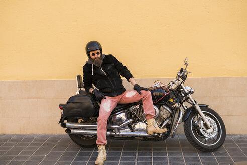 Portrait of bearded biker wearing helmet and sunglasses sitting on his motorcycle - KKAF00498
