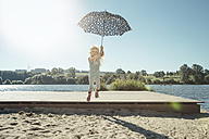 Girl with umbrella jumping off a jetty on a sunny day - IPF00367