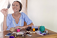 Smiling woman doing handicraft on wooden table - KNTF00736