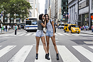 USA, New York City, two twin sisters talking on zebra crossing in Manhattan - GIOF02171