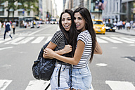USA, New York City, two happy twin sisters in Manhattan - GIOF02174