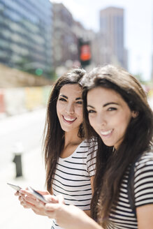 USA, New York City, two happy twin sisters with cell phones in Manhattan - GIOF02180