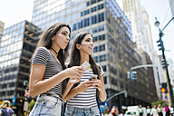 USA, New York City, two twin sisters with cell phones in Manhattan - GIOF02186