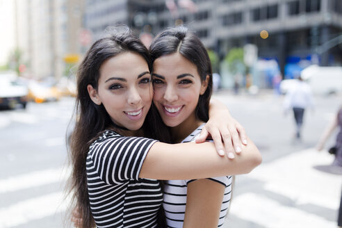 USA, New York City, portrait of two beautiful twin sisters in Manhattan hugging - GIOF02189