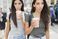 USA, New York City, two twin sisters on the go in Manhattan with takeaway drink - GIOF02195