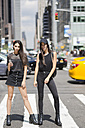USA, New York City, two fashionable twin sisters standing on zebra crossing in Manhattan - GIOF02219