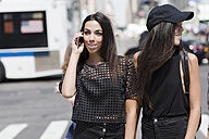 USA, New York City, two fashionable twin sisters with cell phone in Manhattan - GIOF02222