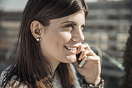 Smiling young woman with hearing aid on the phone - ZEDF00554