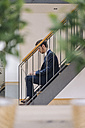 Businessman sitting on stairs using laptop - KNSF01148