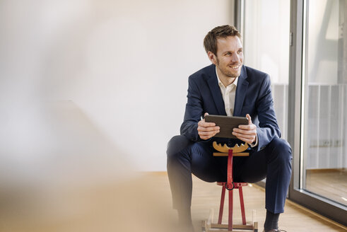Smiling businessman sitting on rocking horse with tablet - KNSF01154
