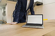 Businessman leaning on table with laptop - KNSF01157