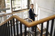 Businessman using tablet in staircase - KNSF01169