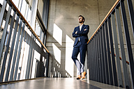 Businessman standing in staircase - KNSF01172