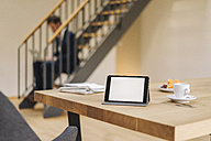 Tablet on table with businessman on stairs using laptop in background - KNSF01187