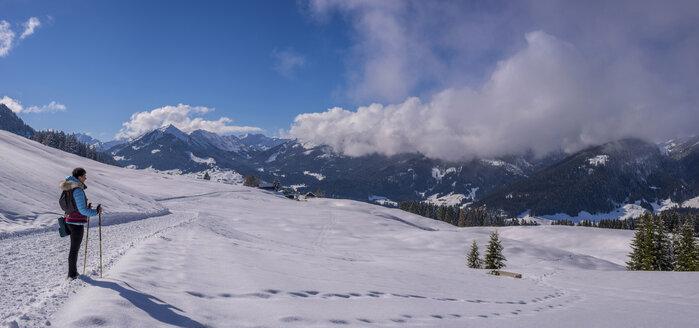 Austria, Kleinwalsertal, woman on high route in winter - WGF01058